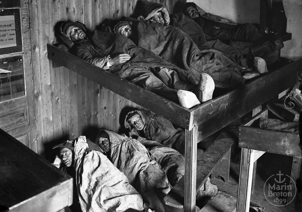 Pêcheurs revêtus du kapo-braz dans leurs couchettes - Abri du marin d'Audierne (1910)