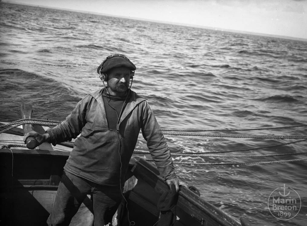 """Pierre Quéméré à la barre du yacht """"Les Abris du Marin"""" avec son casque T. S. F. (1925)"""